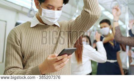 Traveler Wearing Face Mask While Using Mobile Phone On Public Train . Coronavirus Disease Or Covid 1