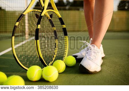 Female tennis player with racket and many balls