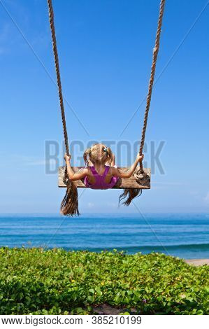 Happy Girl Have Fun Swinging High In Mid Air. Flying Up Upside Down On Rope Swing On Sea Beach. Trav