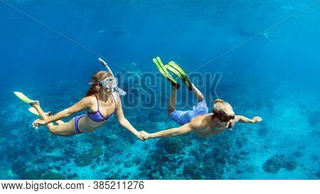 Happy Family Vacation. Young Couple In Snorkeling Mask Hold Hand, Free Dive Underwater With Fishes I
