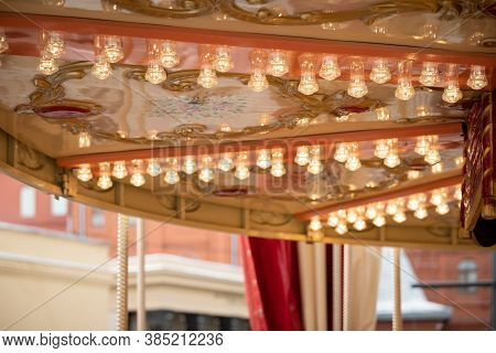 Closeup Of The Lights Of An Old French Carousel In A Leisure Park. Traditional Fairground Vintage Ca