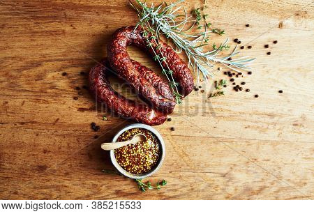 Rustic natural sausages with fresh herbs and french mustard on rustic wooden background. Natural and organic food. Polish cuisine