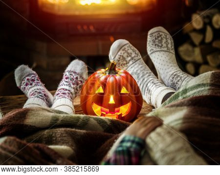 Female and childish feet  are in soft wool socks with burning fireplace at the background. Halloween celebration. Carving jack-o-lantern pumpkin is on the table.