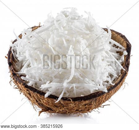 Shredded coconut flakes in the piece of coconut shell isolated on white background. Close-up.