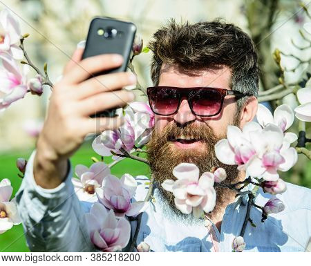 Hipster Happy In Stylish Sunglasses, Taking Selfie Photo, Streaming Video On Smartphone. Man With Be
