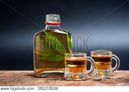 Alcoholic Drink Like Whiskey Brandy Or Schnapps Infused With Cannabis Leaves In The Bottle On The Ta