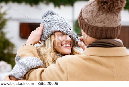 Loving Guy Playing With Knitted Hat Of His Girlfriend During Winter Date Outdoors, Couple Having Fun
