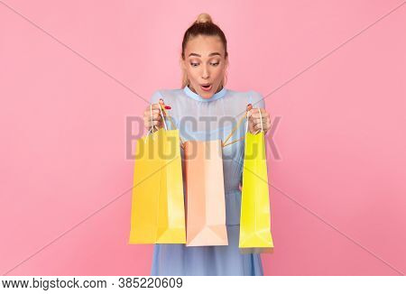 Enjoying Purchase Concept. Portrait Of Excited Curious Woman Holding And Looking Inside Colorful Sho