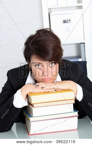 Unmotivated Businesswoman With Pile Of Books
