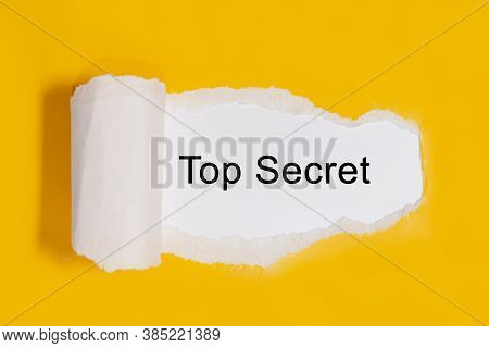 The Text Top Secret Appearing Behind Torn Yellow Paper, The Concept