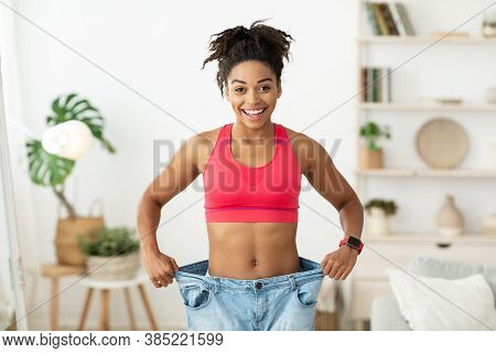 Successful Weight Loss. Happy African Woman After Slimming Showing Her Old Oversize Pants Standing I