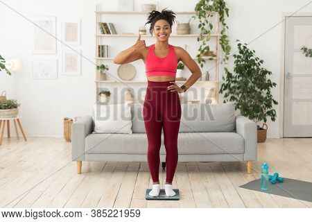 Slimming Concept. Fit African Woman Standing On Weight Scales Gesturing Thumbs Up Posing At Home. Fu