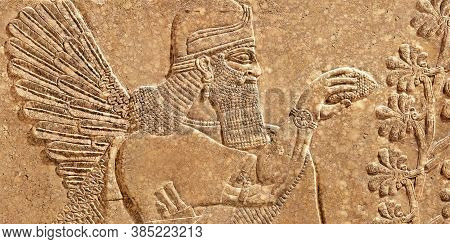 Assyrian Wall Relief Of Winged Genius, Old Carving Panel From Middle East. Remains Of Fine Art Of An