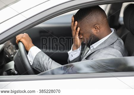 Upset African American Businessman Rubbing His Head While Driving Car. Side View Of Frustrated Young