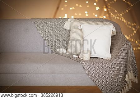 Gray Soft Couch With White Pillows And Cup Of Beverage Against Blurred Brown Wall With Lights As Sym