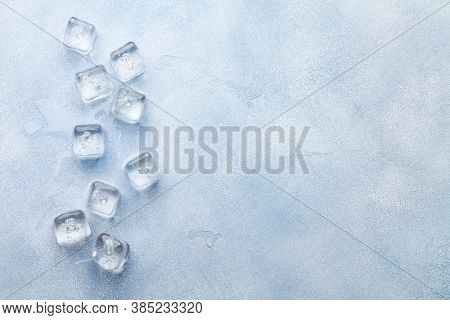 Ice cubes and water drops on stone background. Top view flat lay with copy space