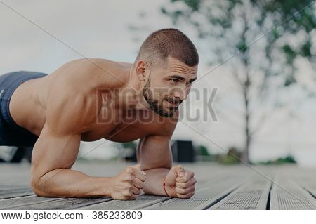 Close Up Shot Of Bearded Motivated Man Stands In Plank, Trains Muscles And Wants To Have Strong Body