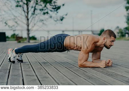 Motivated Male Athlete Does Abs Exercise, Enjoys Bodybuilding Training Outdoor And Stands In Plank.