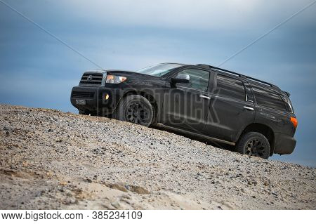 Novyy Urengoy, Russia - September 6, 2020: Black Offroad Suv Toyota Sequoia Climbing A High Sandy Hi