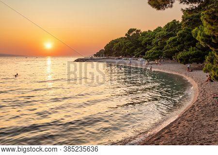 Makarska, Croatia - September 5, 2019: Beautiful beach at Adriatic Sea in Makarska Riviera at sunset, Dalmatia, Croatia