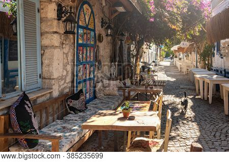 Alacati, Turkey - November 2, 2019: Picturesque street in Mediterranean Alacati Town in Turkey. Alacati is popular historical tourists destination in Turkey. Cozy outdoor cafe and restaurants