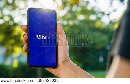 Berlin, Germany August 2019: Woman Hand Holding Iphone Xs With Logo Of Libra In The Park. Libra Face