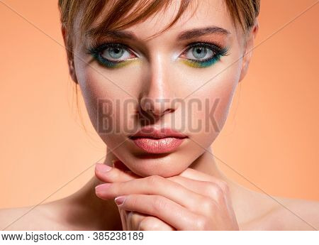 Beautiful girl with trandy makeup. Face of an young girl close-up with a green color makeup. Stylish makeup.