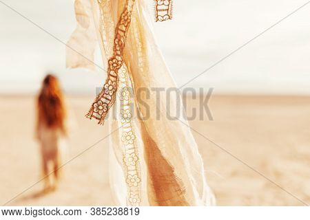 Close Up Of Beige Fabric And Lace Foreground And Young Beatiful Woman At Background On The Beach At