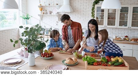 Healthy Eating. Young Beautiful Family Cooking Together In The Modern Kitchen At Home. Mother And Fa