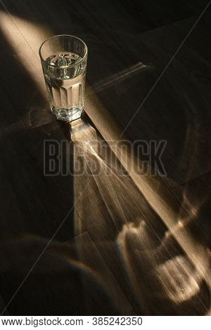 Abstract Glass Of Water And Sunrays On Wooden