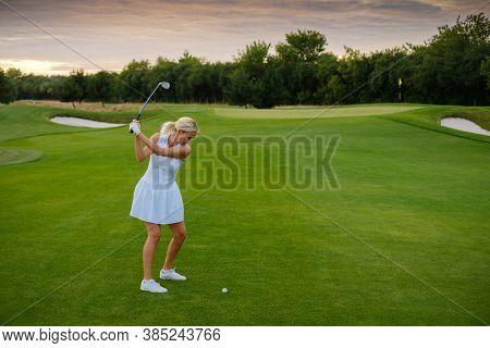 Lady in White Uniform Hit Golf Ball .