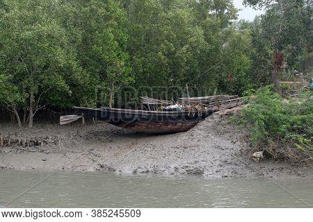 SUNDARBANS, INDIA - FEBRUARY 25, 2020: Boat on mud banks, Mangrove forest, Sundarbans, Ganges delta, West Bengal, India