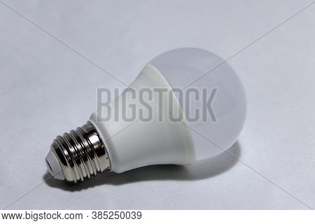 White Light Bulb On The White Background. It Is A Glass Bulb Inserted Into A Lamp Or A Socket In Cei