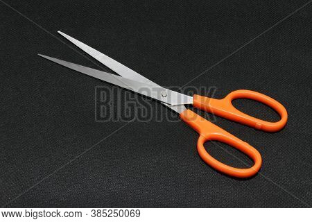 Metal Scissors Orange Handle Put On The Black Background. It Is An Instrument Used For Cutting, Cons