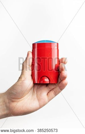 Red Deodorant In Male Hand Isolated On White Background. Mens Deodorant, Personal Hygiene Products,