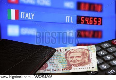 One Thousand Lire Of Italy Banknote With Black Wallet On The Calculator With Digital Board Of Curren