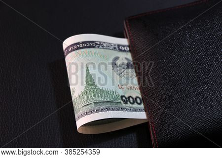 One Thousand Of Banknote Currency Lao Kip With Black Wallet On The Black Floor, It Is The Money Of L