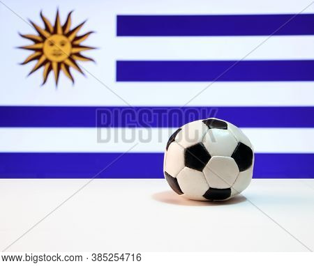 Small Football On The White Floor And Uruguayan Nation Flag Background. The Concept Of Sport, Urugua