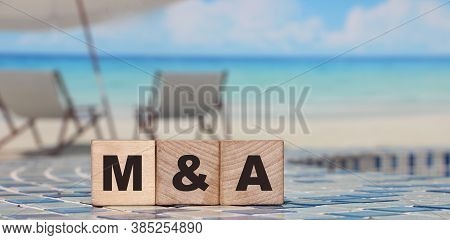 M And A Or Merger And Acquisition Text Written On A Wooden Cubes. Business Concept