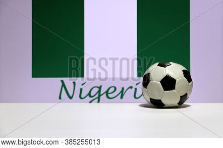 Small Football On The White Floor And Nigerian Nation Flag With The Text Of Nigeria Background. The