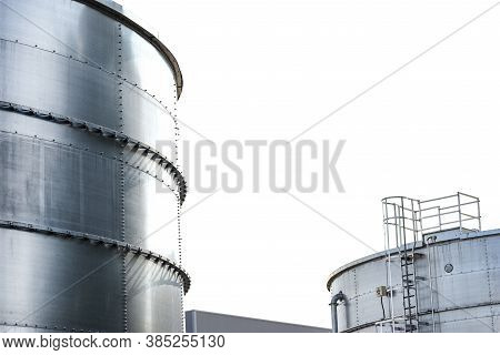 Steel Industrial Silos For Liquids And Solids Standing In A Factory, White Sky In The Background.