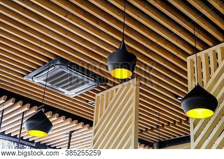 Three Black Pendant Lamps And Ceiling Air Conditioner In A Wooden Interior. Yellow Lights Hang Overh
