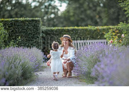 Beautiful Young Mother And Her Little Daughter In Blooming Lavender. International Family. Mom And D