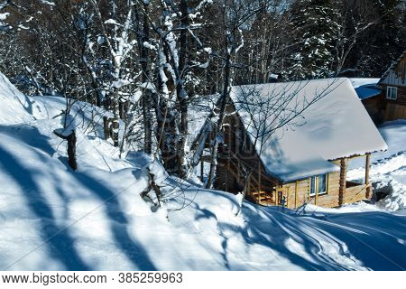 A Small Wooden House Stands In The Forest, Covered With White Snow. Winter, Frost Everywhere There I