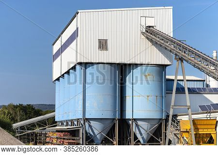 Big Blue Metallic Industrial Silos For The Production Of Cement At An Industrial Cement Plant On The