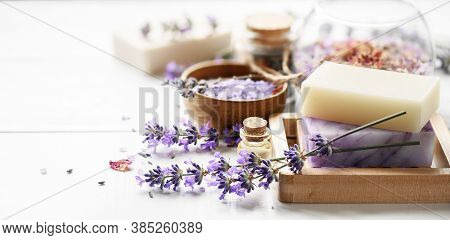 Lavender Spa Products And Lavender Flowers On A White Table. Handmade Soap On Wooden Soap Dish, Esse