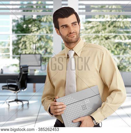 Portrait of handsome businessman in modern office, smiling.
