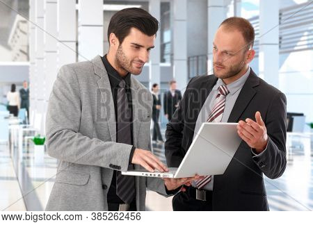 Corporate businessmen working with laptop in office lobby, having meeting, talking.