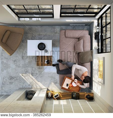 Man sitting on sofa at home in modern room, having breakfast at morning. above the head view.