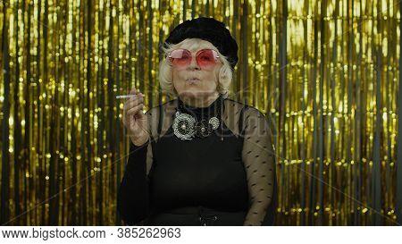 Elderly Style Granny Caucasian Mature Woman In Sunglasses Posing, Smoke Cigarette On Golden Backgrou
